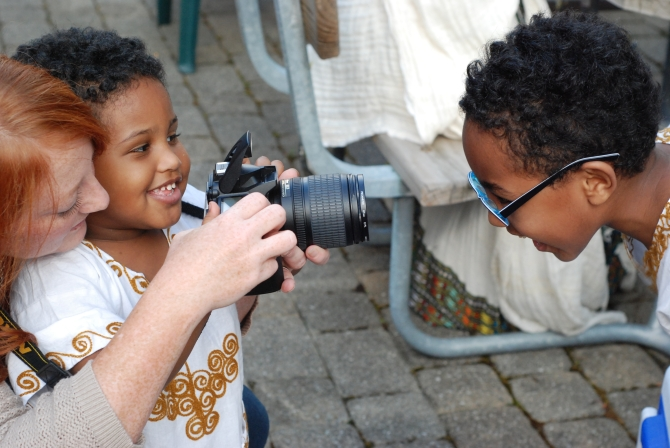 The Kassa's younger son takes a picture of their oldest, with the help of a friend.